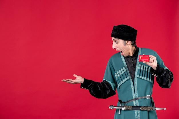 Portret azerskiego mężczyzny w tradycyjnym stroju trzymającego kartę kredytową na czerwone pieniądze etniczne novruz