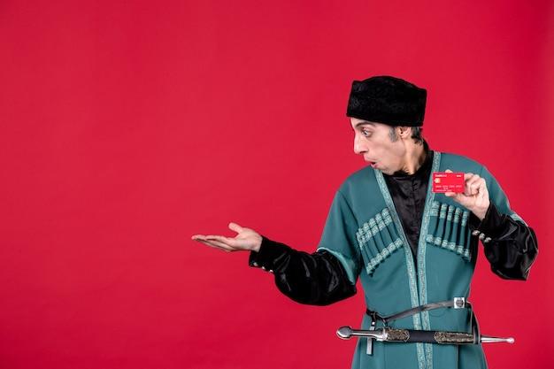 Portret azerskiego mężczyzny w tradycyjnym stroju trzymającego kartę kredytową na czerwone wiosenne pieniądze etniczne novruz