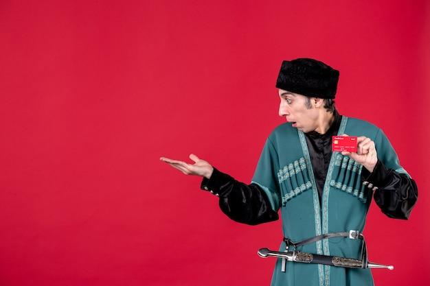 Portret azerskiego mężczyzny w tradycyjnym stroju trzymającego kartę kredytową na czerwonym kolorze wiosennych pieniędzy etnicznych novruz