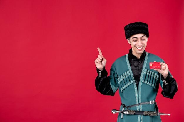 Portret azerskiego mężczyzny w tradycyjnym stroju trzymającego kartę kredytową na czerwonym wiosennym etnicznym kolorze novruz
