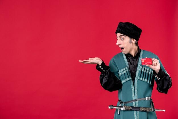 Portret azerskiego mężczyzny w tradycyjnym stroju trzymającego kartę kredytową na czerwonym wiosennym etnicznym novruz