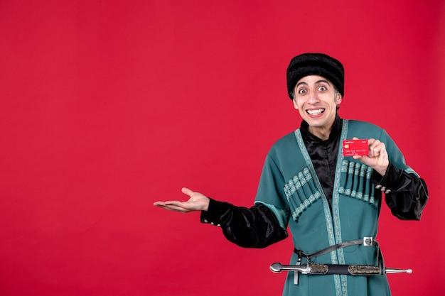 Portret azerskiego mężczyzny w tradycyjnym stroju, trzymającego kartę kredytową na czerwonym wiosennym pieniądzu etnicznym