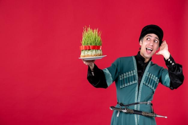 Portret azerskiego mężczyzny w tradycyjnym stroju trzymającego zielone nasienie na czerwonym etnicznym świątecznym tancerzu novruz