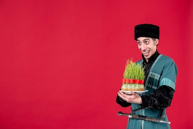 Portret azerskiego mężczyzny w tradycyjnym stroju, trzymającego zielone nasienie na czerwonym tancerzu etniczne wakacje novruz