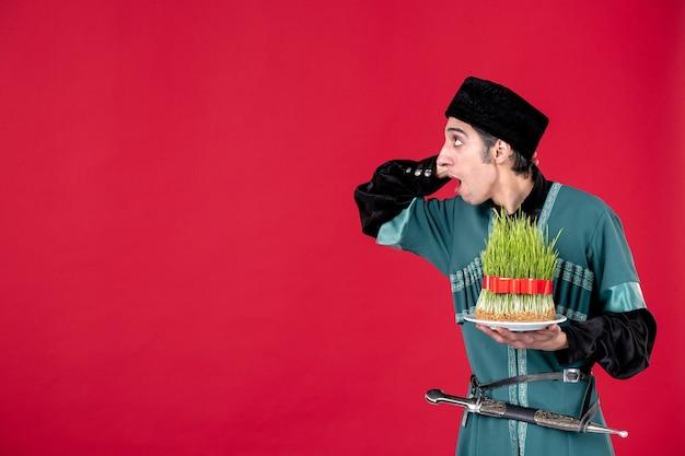 Portret azerskiego mężczyzny w tradycyjnym stroju z nasieniem na czerwonej tancerce etnicznej wiosny novruz