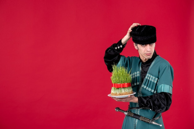 Portret azerskiego mężczyzny w tradycyjnym stroju z nasieniem na czerwonej wakacyjnej etnicznej tancerce wiosna novruz
