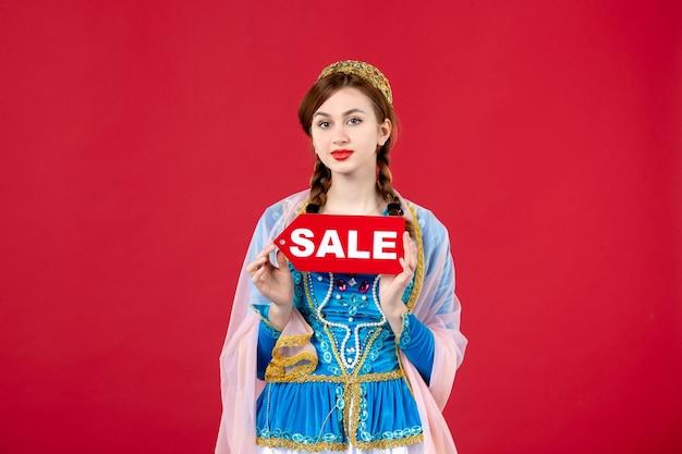 Portret azerskiej kobiety w tradycyjnej sukience trzymającej tabliczkę znamionową sprzedaży na czerwono