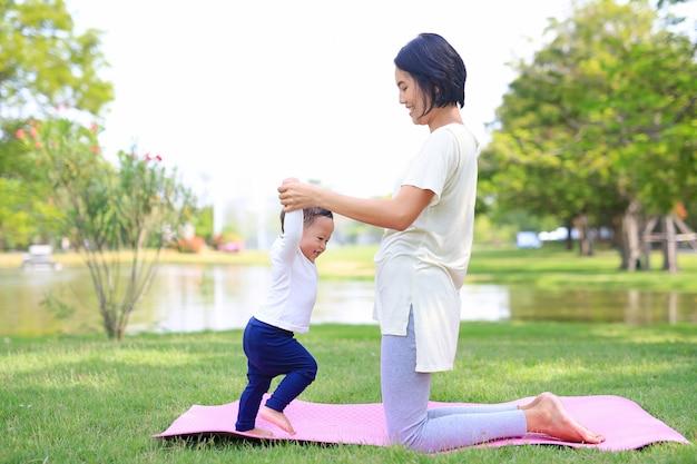 Portret azjata matki robi dziecka joga dla jej syna na zielonym gazonie w natura ogródzie plenerowym.