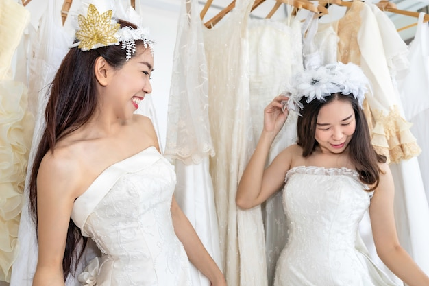 Portret azjatycka homoseksualna para w panny młodej sukni wybiera suknię w sklepie. pojęcie lgbt lesbijka.