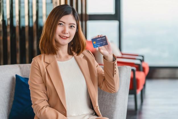 Portret azjatycka kobieta przedstawia kartę kredytową dla zakupy online w nowożytnym lobby lub przestrzeni roboczej
