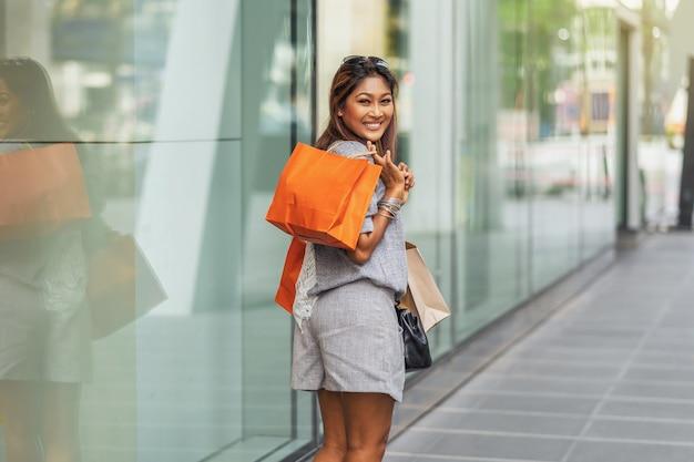 Portret azjatycka kobieta spacerująca i robiąca zakupy obok sklepu z szczęśliwą akcją