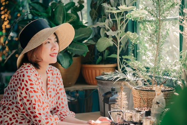 Portret azjatycka kobieta z kapeluszowy ono uśmiecha się w lata sklep z kawą cukiernianym rocznika koloru brzmieniu.