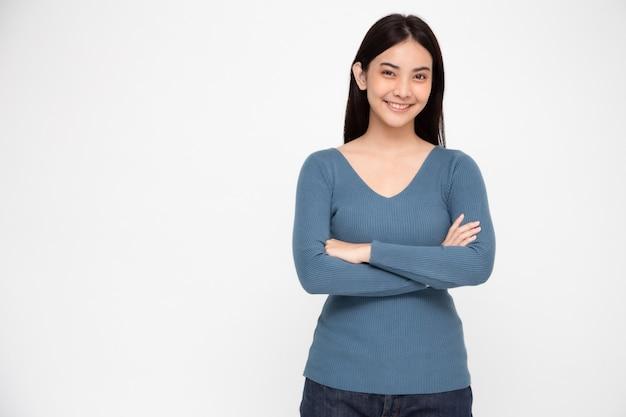 Portret azjatycka kobieta z rękami krzyżować i uśmiechem odizolowywającymi, młodej dziewczyny ono uśmiecha się