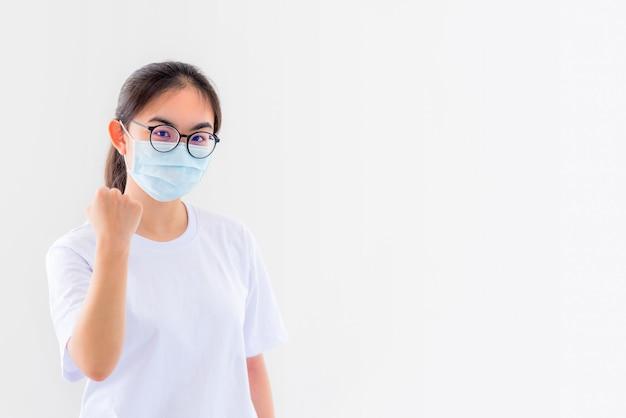 Portret azjatycka młoda kobieta nosi okulary i maskę, aby chronić się przed koronawirusem, dziewczyna pokazuje pięść, zachęcając do walki z chorobą zakaźną, koncepcja zatrzymania wirusa covid 19, aby wygrać na białym tle