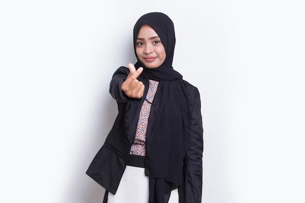 Portret azjatycka muzułmańska kobieta nosi hidżab pokazując znak miłości serca na białym tle