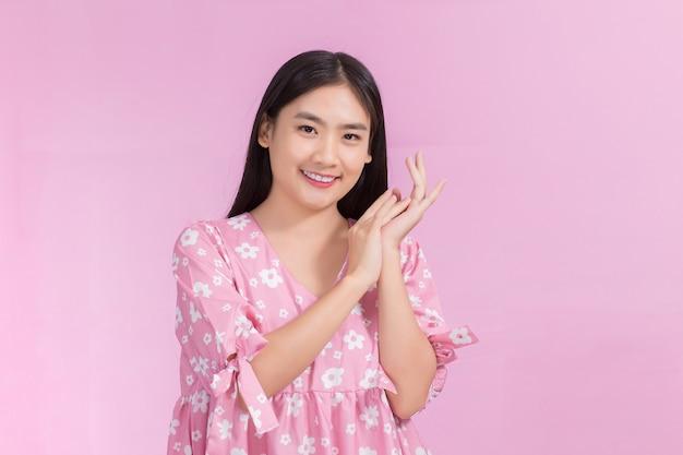 Portret azjatycka piękna kobieta w różowej sukience i czarnych długich włosach jej dłonie dotykają policzka uśmiechu