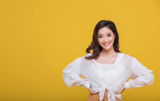 Portret azjatycka piękna szczęśliwa młoda kobieta ono uśmiecha się rozochoconą i patrzeje kamerę odizolowywającą na żółtym pracownianym tle