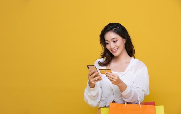 Portret azjatycka piękna szczęśliwa młoda kobieta ono uśmiecha się rozochocony i trzyma kredytową kartę i używa mądrze telefon dla robić zakupy online z torba na zakupy na żółtym tle.