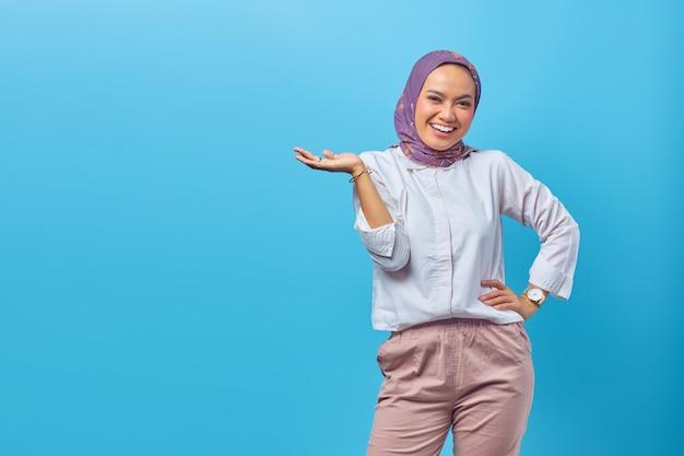 Portret azjatycka piękna szczęśliwa młoda kobieta uśmiecha się wesoło i patrzy na kamerę odizolowaną na niebieskim tle