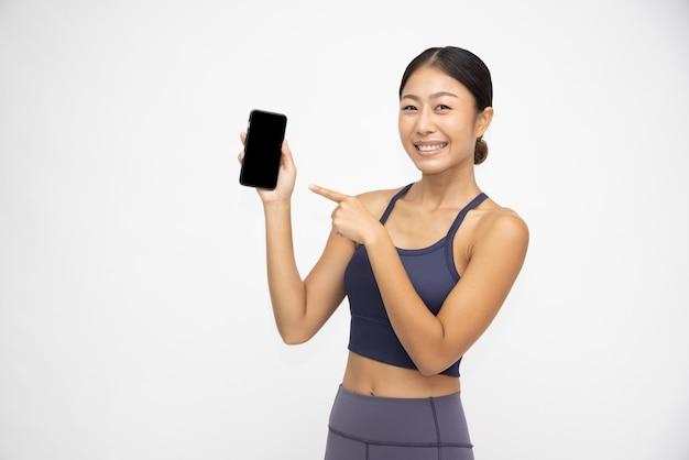 Portret azjatycka sportowa kobieta pokazuje telefon komórkowy odizolowywający nad białym tłem