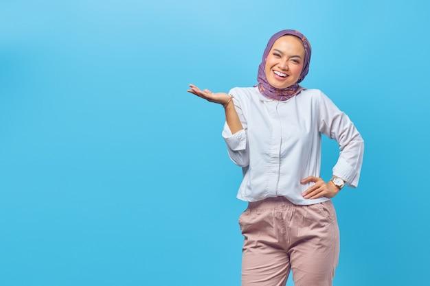 Portret azjatycka szczęśliwa młoda kobieta uśmiecha się wesoło i patrzy na kamerę odizolowaną na niebieskim tle