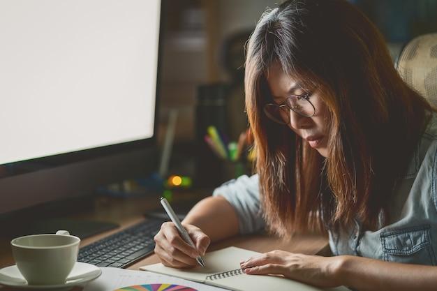 Portret azjatycki bizneswomanu obsiadanie i działanie mocno na stole z przodem comput