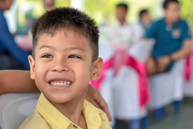 Portret azjatycki chłopiec wisecracking i rozmyty tło.