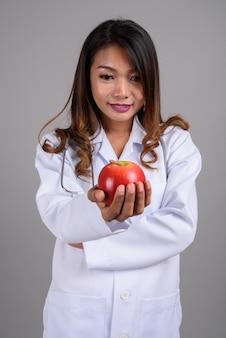 Portret azjatycki lekarz kobieta trzyma jabłko