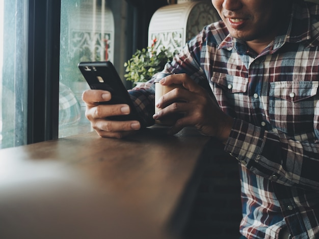 Portret azjatycki mężczyzna w używać mądrze telefonu sklep z kawą.
