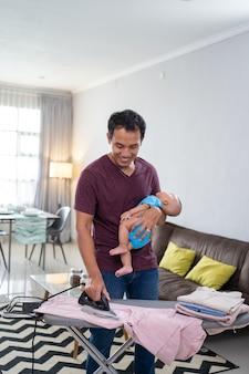 Portret azjatycki ojciec prasowanie ubrań, trzymając na ręku swoje niemowlę niemowlę