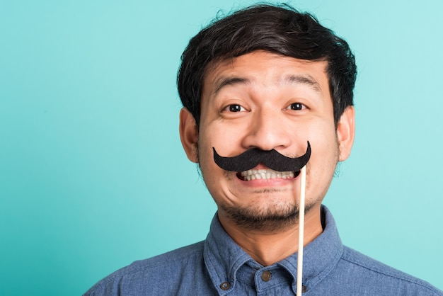 Portret azjatycki szczęśliwy przystojny mężczyzna pozuje trzyma śmieszną kartę wąsy lub rocznika fałszywe wąsy na ustach