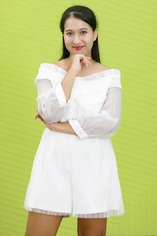 Portret azjatycki uśmiechnięta kobieta ubrana w białą sukienkę. lady asia stoi z ufnością w zielonym tle.