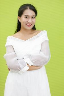 Portret azjatycki uśmiechnięta kobieta ubrana w białą sukienkę. pani azja stojąca rozciąga się i przytula się do piersi z pewnością siebie na zielonym tle.