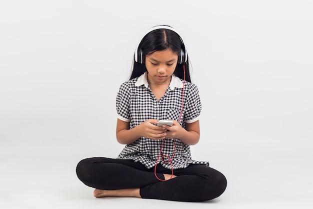 Portret azjatyckich dzieci dziewczyna siedzi, słuchając muzyki na białym tle