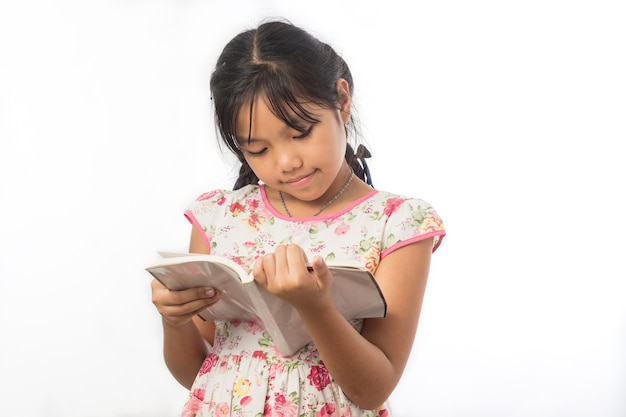 Portret azjatyckich dziewczynka trzyma książkę na białym tle