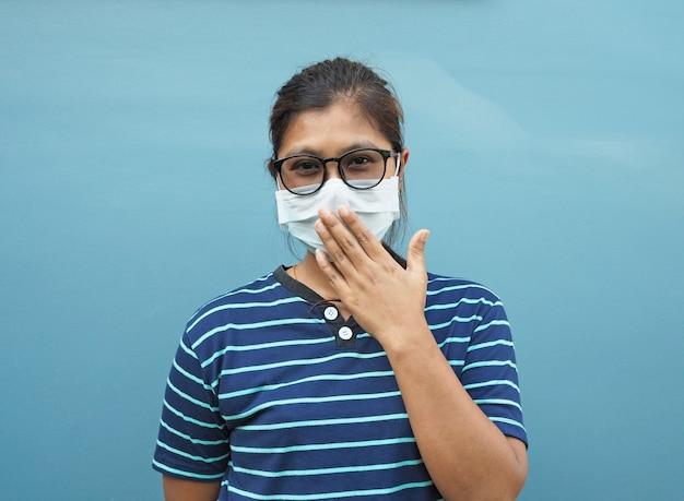 Portret azjatyckich kobiet noszących okulary i maski ochronne. zakrywając usta na niebieskim tle