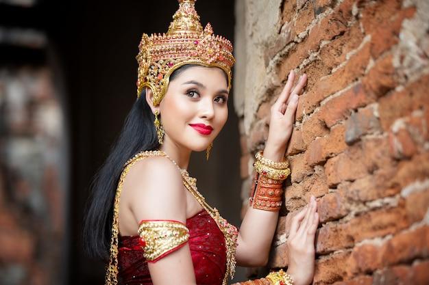 Portret azjatyckich kobiet w strojach tradycyjnego tancerza tajskiego stoi przed starożytnym posągiem buddy. ayuttaya historical park, tajlandia azja.