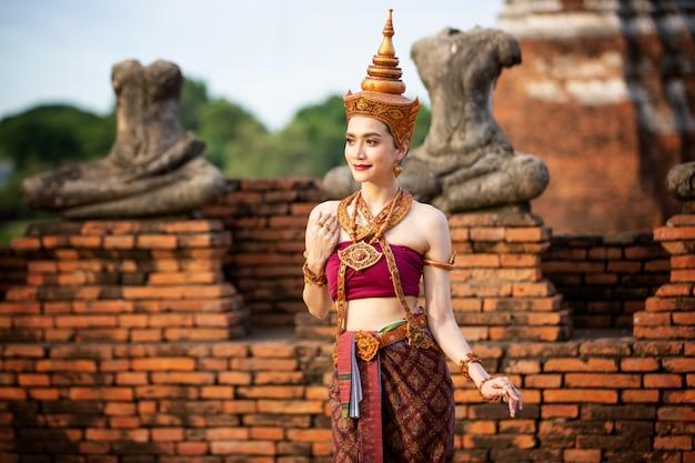 Portret azjatyckich kobiet w strojach tradycyjnego tancerza tajskiego stoi przed starożytnym posągiem buddy. park historyczny ayuttaya, tajlandia