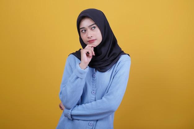 Portret azjatyckich piękna kobieta ubrana w czarny hidżab marszczy brwi i myśli coś gest