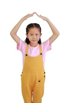 Portret azjatyckie młoda dziewczyna z rękami nad głową, dzięki czemu gest dachu domu na białym tle. koncepcja opieki i ochrony dziecka