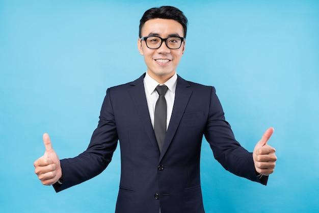 Portret azjatyckiego biznesmena dając kciuki do góry na niebieskiej ścianie