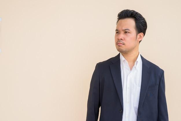 Portret azjatyckiego biznesmena noszącego garnitur na prostym tle podczas myślenia