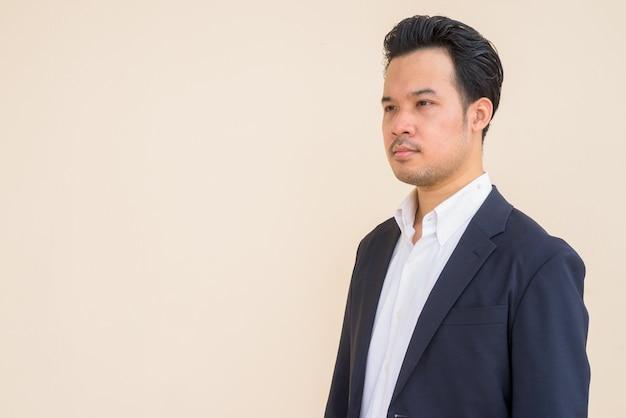 Portret azjatyckiego biznesmena noszącego garnitur na zewnątrz na prostym tle