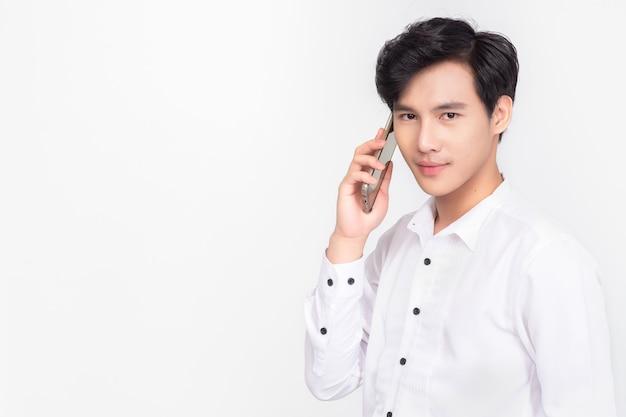 Portret azjatyckiego biznesmena rozmawia inteligentny telefon na białym tle