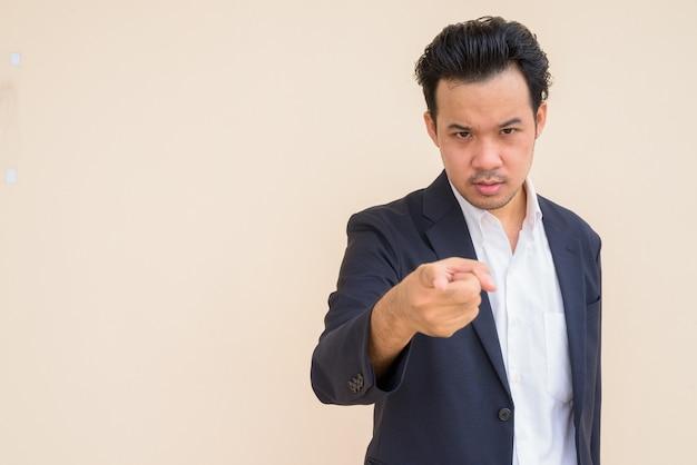 Portret azjatyckiego biznesmena w garniturze na prostym tle i wskazującym palcem na aparat