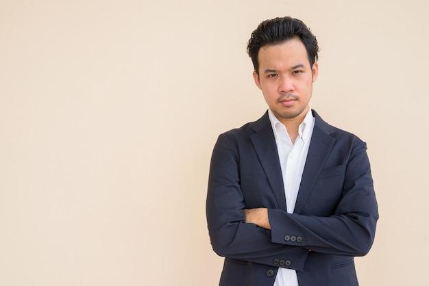 Portret azjatyckiego biznesmena w garniturze z rękami skrzyżowanymi na prostym tle