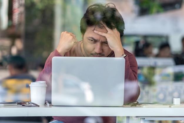 Portret azjatyckiego biznesmena w garniturze za pomocą laptopa technologicznego do poważnej pracy