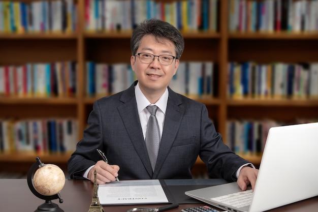 Portret azjatyckiego biznesmenem w średnim wieku siedzi przy biurku.