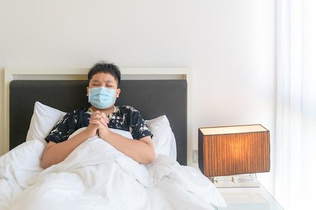 Portret azjatyckiego chłopca noszącego maskę i modlącego się o zatrzymanie covid-19 podczas epidemii koronawirusa