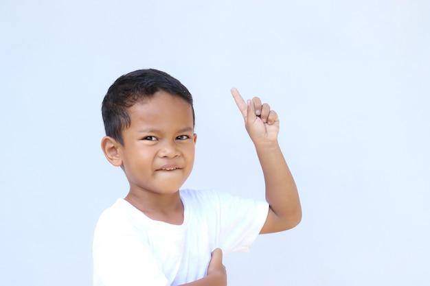 Portret azjatyckiego chłopca, wskazując na coś. z kopią miejsca na prezentację produktu, reklamę i nie tylko